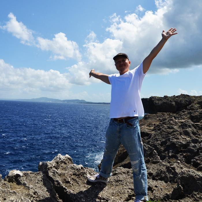 海をバックに、崖の上で気持ちよさそうに両手を広げる北野啓太郎