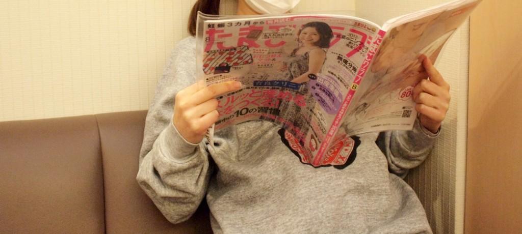 産婦人科で雑誌「たまごクラブ」を読む妊婦