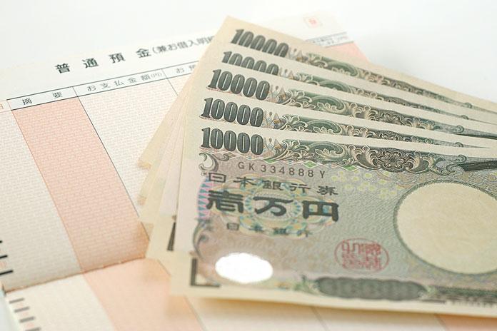 1万円札と貯金通帳