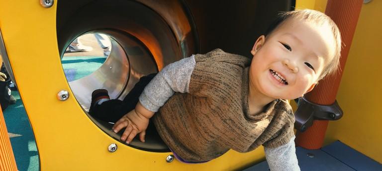 にこにこパーク すべり台から顔を覗かせる1歳の息子