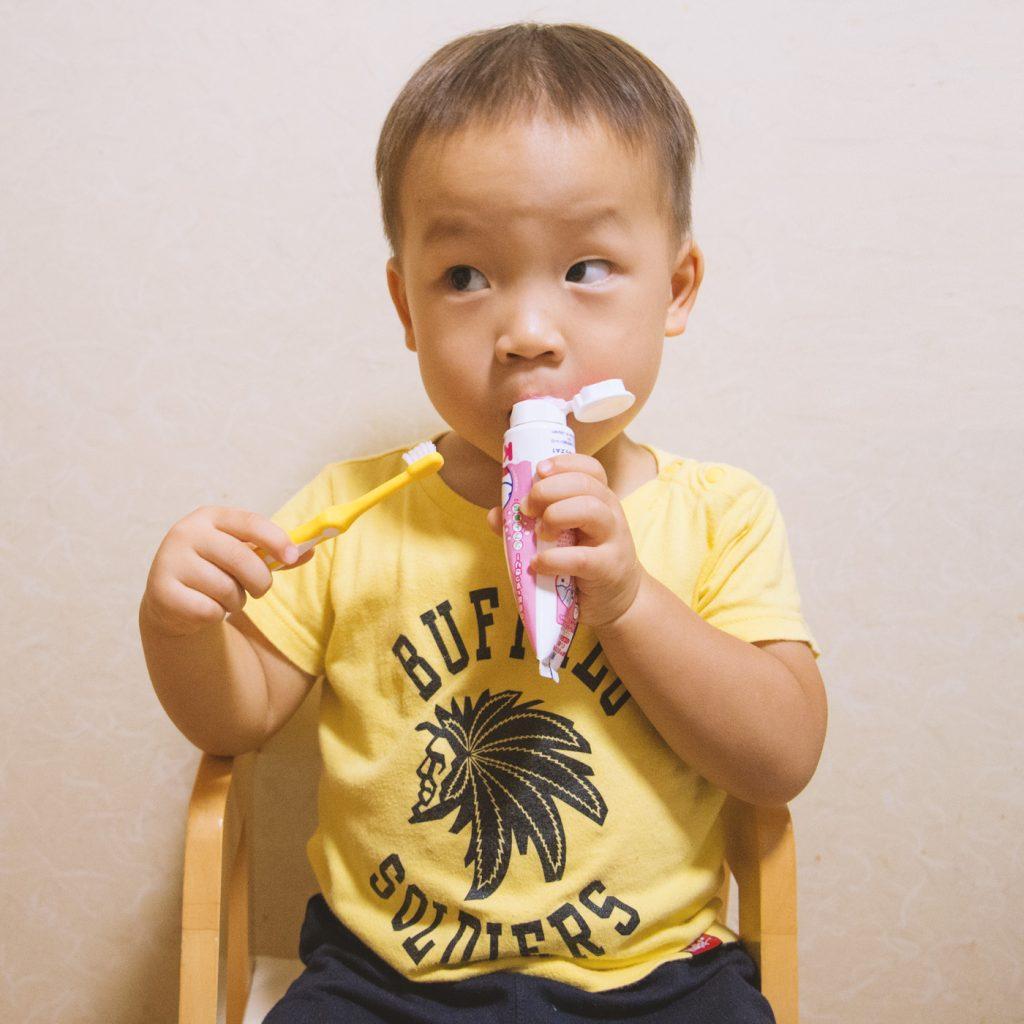 椅子に座って歯磨きする子供