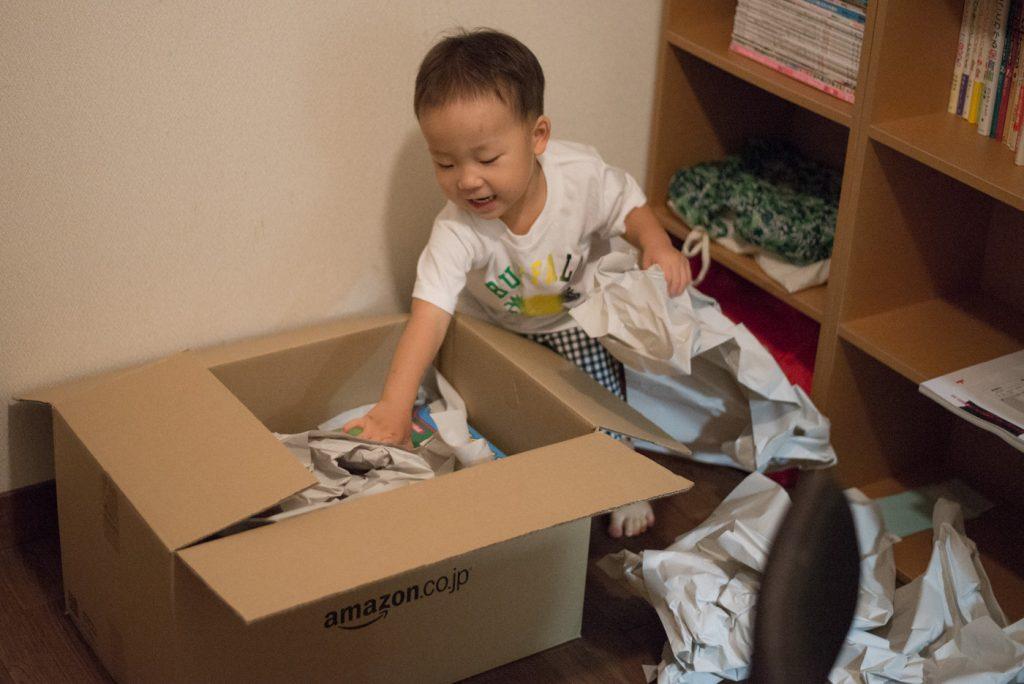 Amazonから届いたダンボールを開ける息子