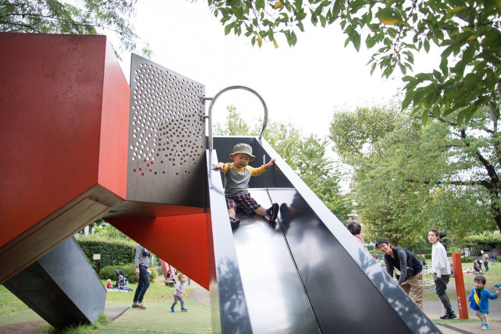 港区立檜町公園の滑り台をすべる子供