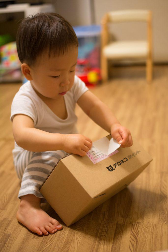 クロネコヤマトの宅急便から届きた荷物を開ける息子。2歳