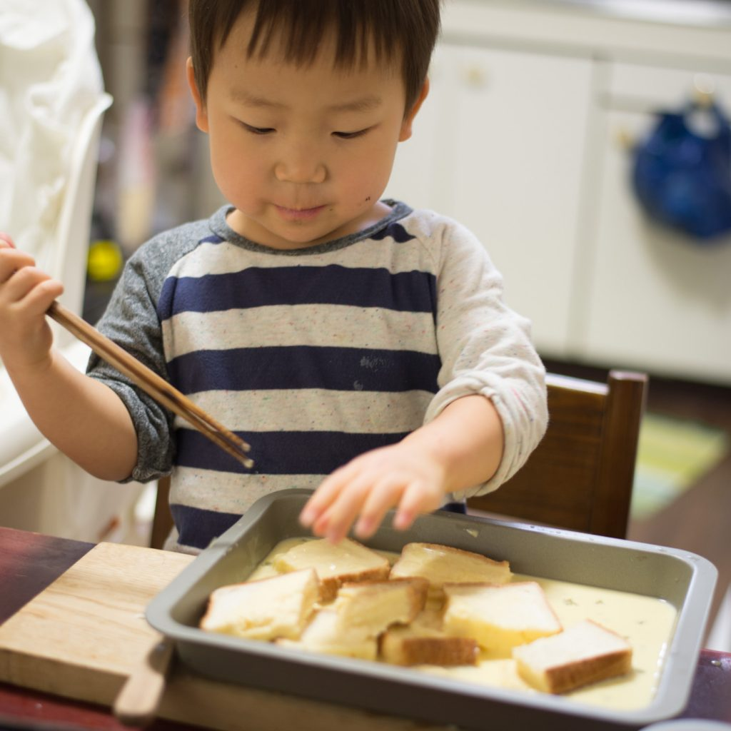 2歳の料理「フレンチトースト」切ったパンを牛乳とたまごに浸します