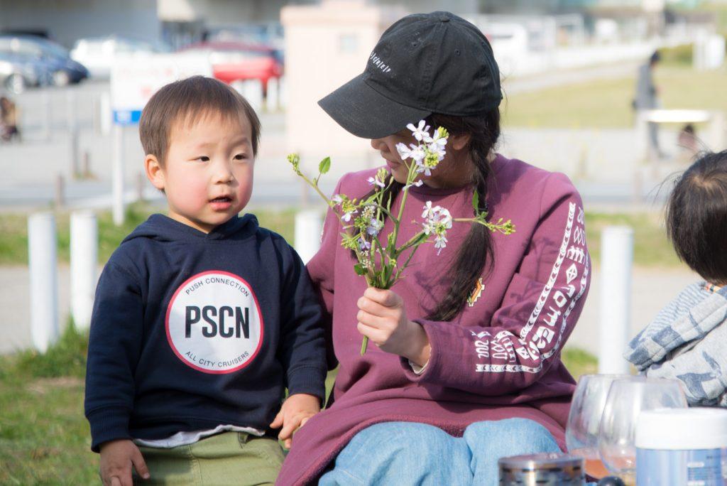 摘んだ花をママにプレゼントする2歳の息子