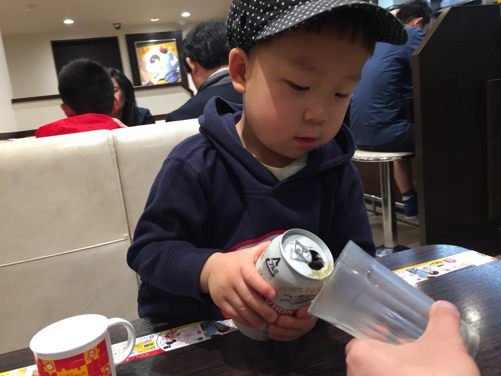 パパにビールを注ぐ子供。カレーハウスCoCo壱番屋で、お子さまカレー。