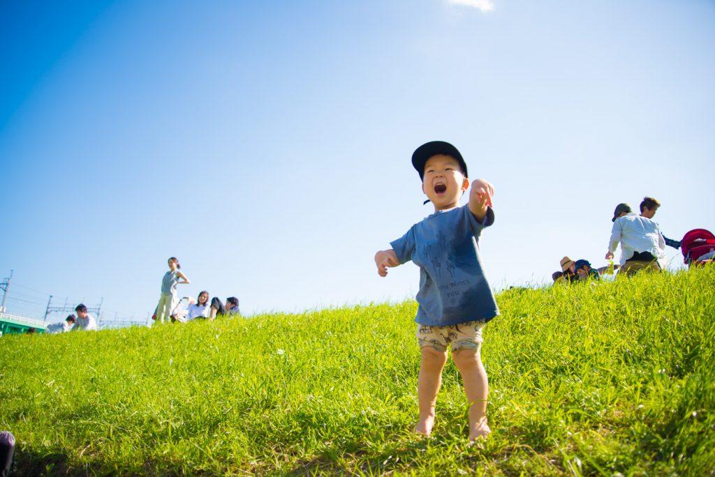 多摩川で土手でうれしくで叫ぶ子供