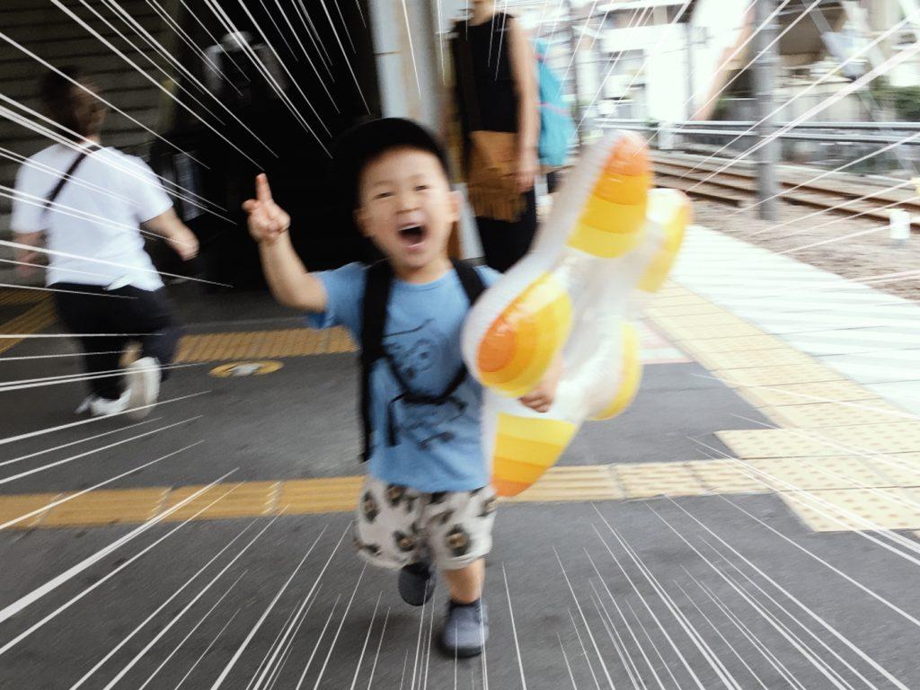 浮き輪をもって電車に乗り込む息子(3歳)