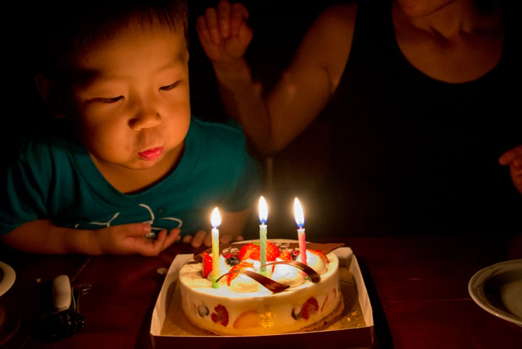 結婚7年8ヶ月9日記念日のケーキを真っ暗のなかろうそくをフーッと消す息子