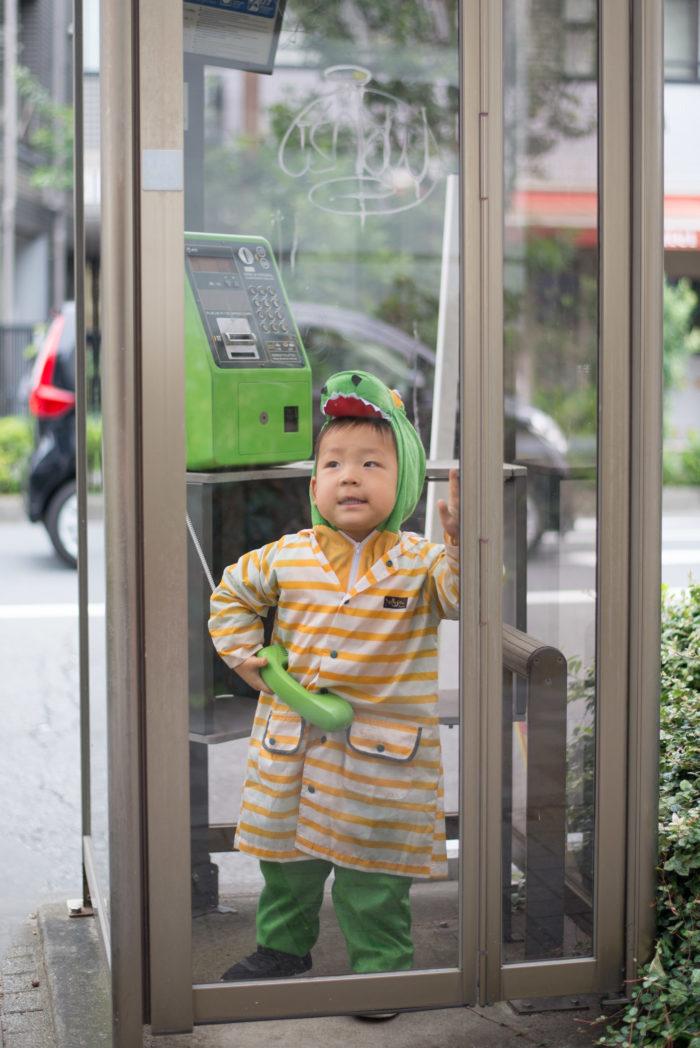 恐竜の着ぐるみを着て電話ボックスに入る息子