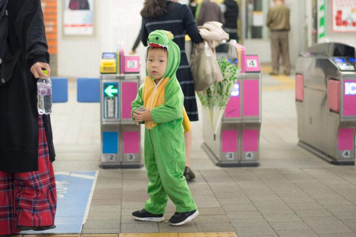 駅の改札で恐竜の着ぐるみを着る息子