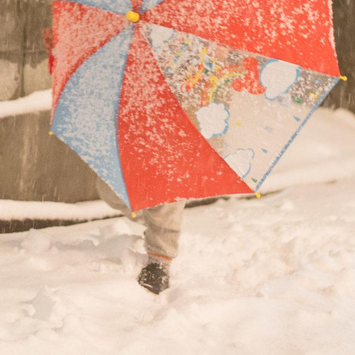 吹雪くの中を歩く3歳の子供