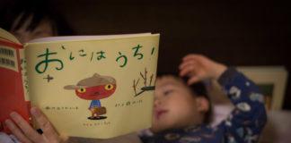 ママと一緒にベッドで絵本を読んでいる3歳の息子