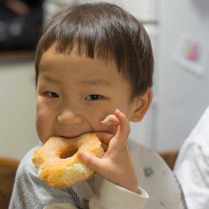 3歳の鼓太郎が、嬉しそうにドーナツを食べている