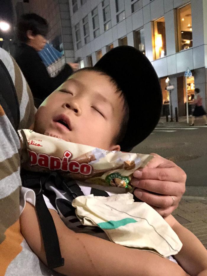 寝ている息子と、打撲した顎をパピコで冷やすパパ
