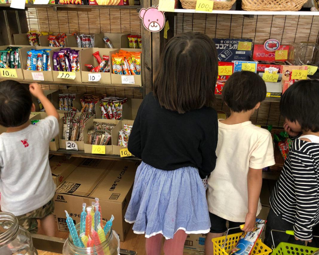 駄菓子屋さんで、お菓子を選ぶ子どもたち