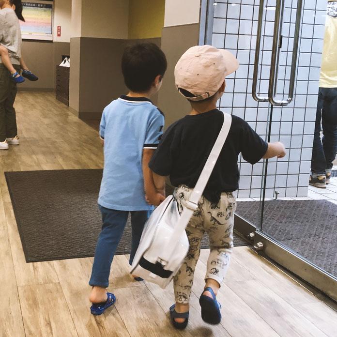 お友達と手をつないで、水泳教室から一緒に帰る4歳の息子