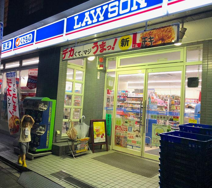 ローソンの店の前で、突然の雨に頭をおさえる男の子