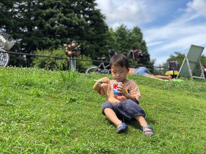 芝生の上でかき氷を食べる子ども