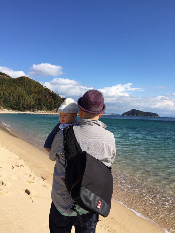 赤ちゃんを抱っこして海岸を歩くパパ