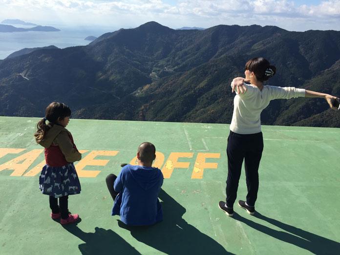 嵩山からのパラグライダー発射台でくつろぐ大人と子ども 足元にTAKE OFFの文字