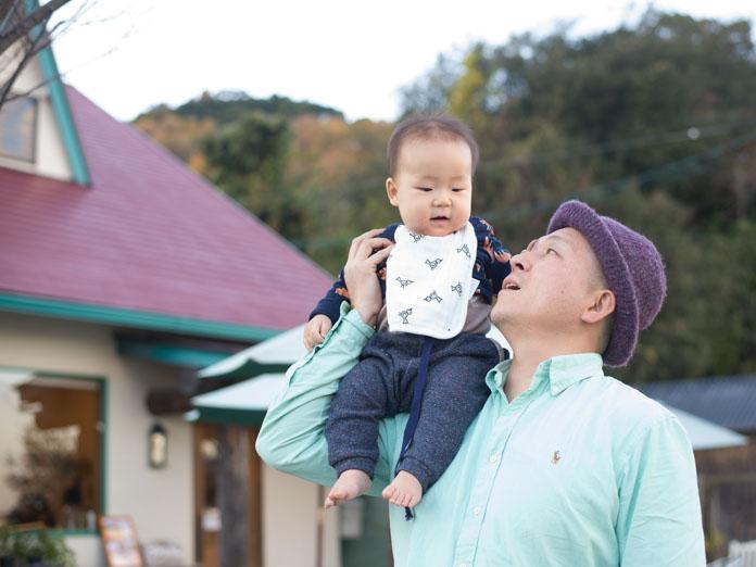 ジャム屋さんの前で、子どもを方に乗せて立つパパ