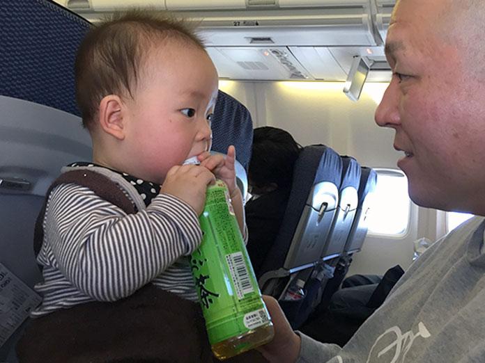 飛行機の中で、0歳の赤ちゃんと同じ座席に座るパパ