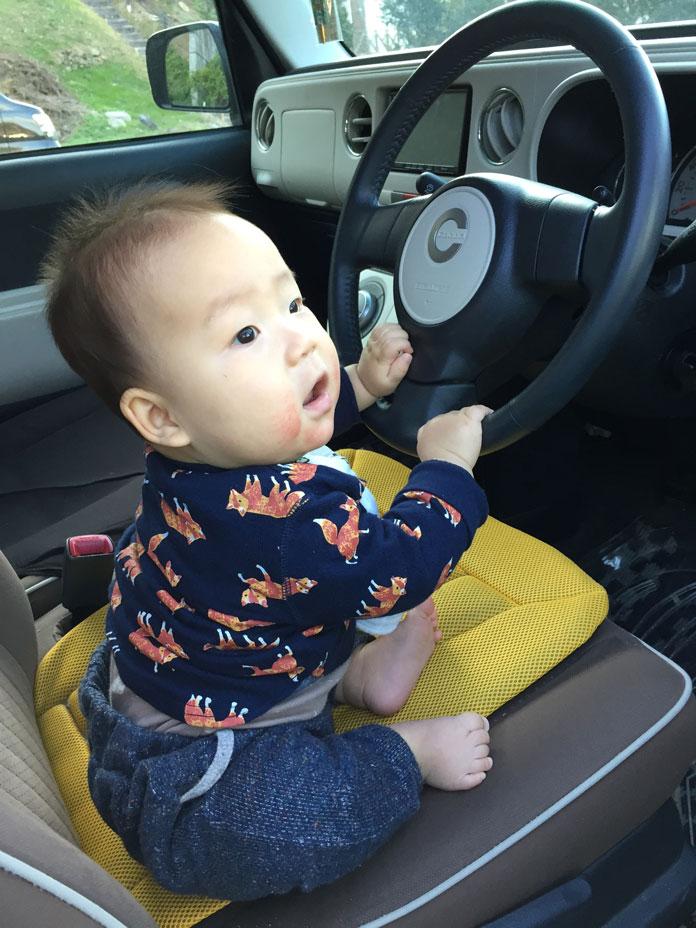 車の運転席に座って、ハンドルを握る赤ちゃん