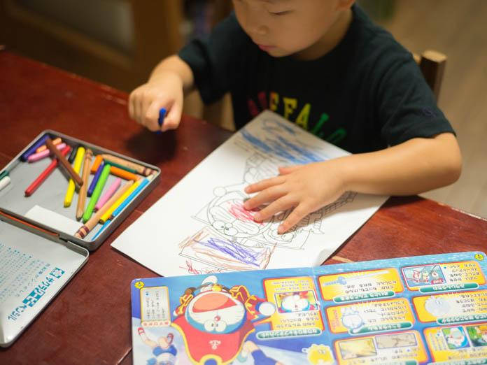ドラえもんの絵本を参考に、ドラえもんの塗り絵をする男の子