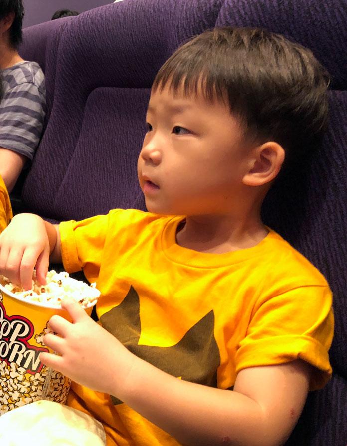 映画館の座席で、ポップコーンを食べる息子