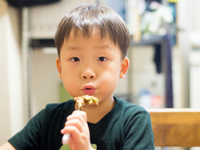カラルーお好み焼きを、ふーふーしながら食べる4歳の男の子