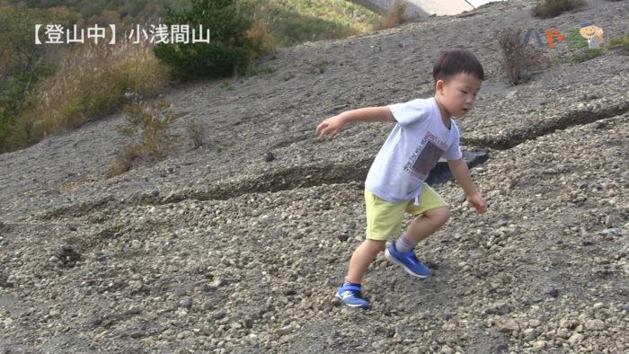 砂利の山道を必死で歩く4歳の子ども