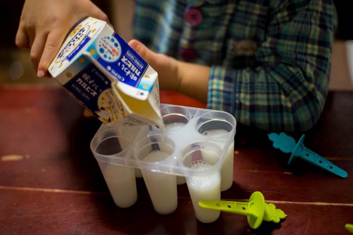 アイスキャンデーメーカーにジュースを注ぐ