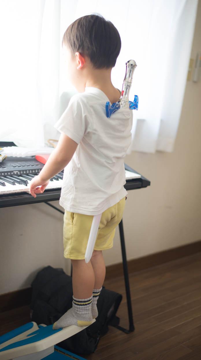 背中に剣をさして、電子キーボードの前に立つ息子