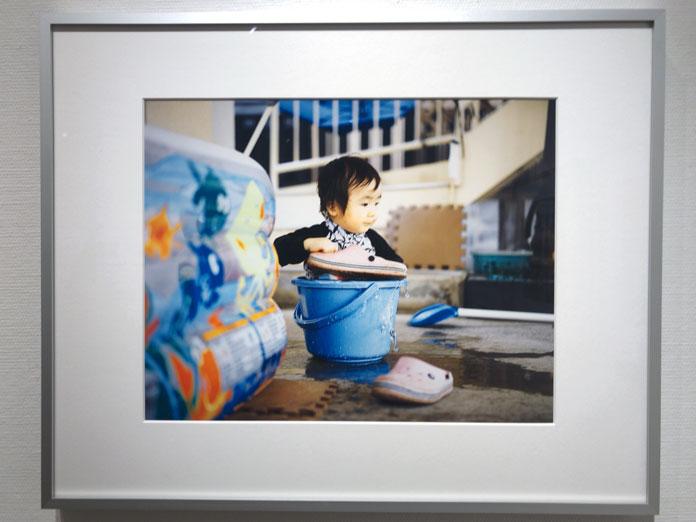 バケツで水遊びする子ども 幡野広志 作品展「優しい写真」