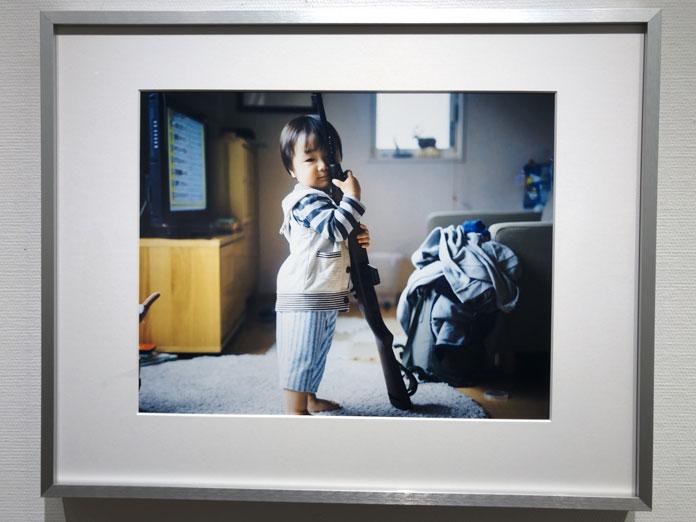 おもちゃの鉄砲を持つ子ども 幡野広志 作品展「優しい写真」