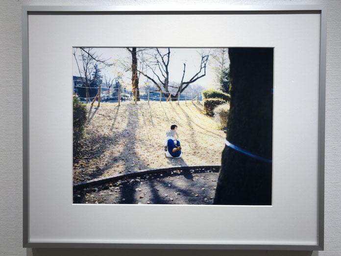 草むらを滑って遊ぶ子ども 幡野広志 作品展「優しい写真」