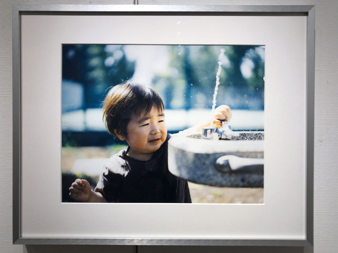 公園の水道で水を出す男の子 幡野広志 作品展「優しい写真」