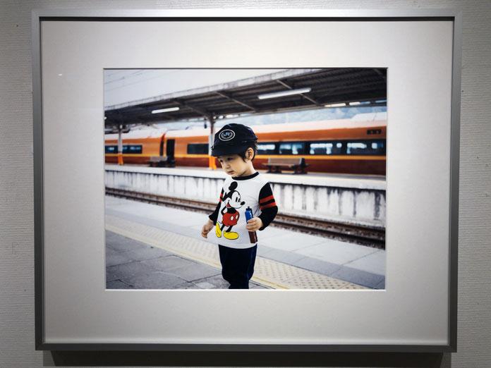 電車のプラットホームに立つ男の子。片手に電車のおもちゃ 幡野広志 作品展「優しい写真」