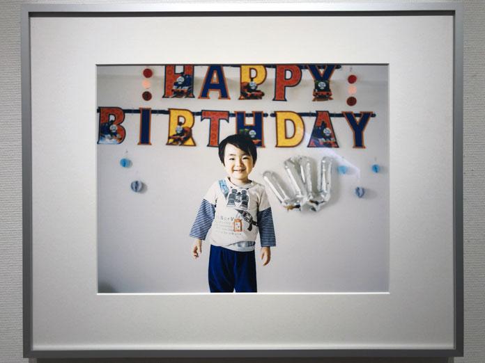 笑顔の男の子と、壁に装飾したHAPPY BIRTHDAY 幡野広志 作品展「優しい写真」