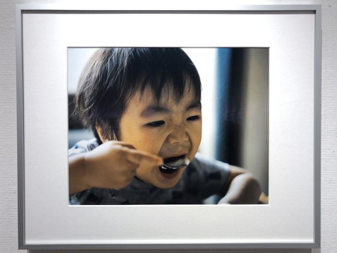大きな口をあけてスプーンをほおばる男の子 幡野広志 作品展「優しい写真」