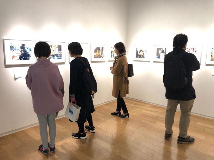幡野広志 作品展「優しい写真」の会場で写真に見入る人たち