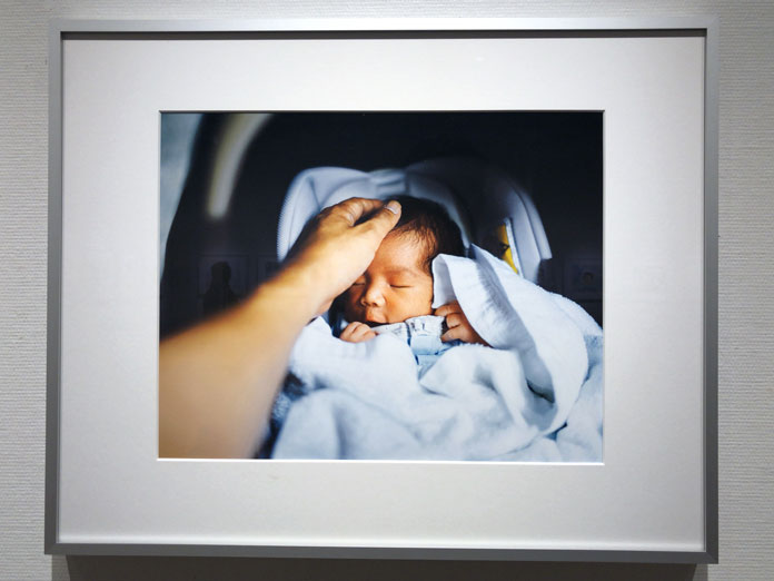 新生児の頭に手を伸ばす 幡野広志 作品展「優しい写真」