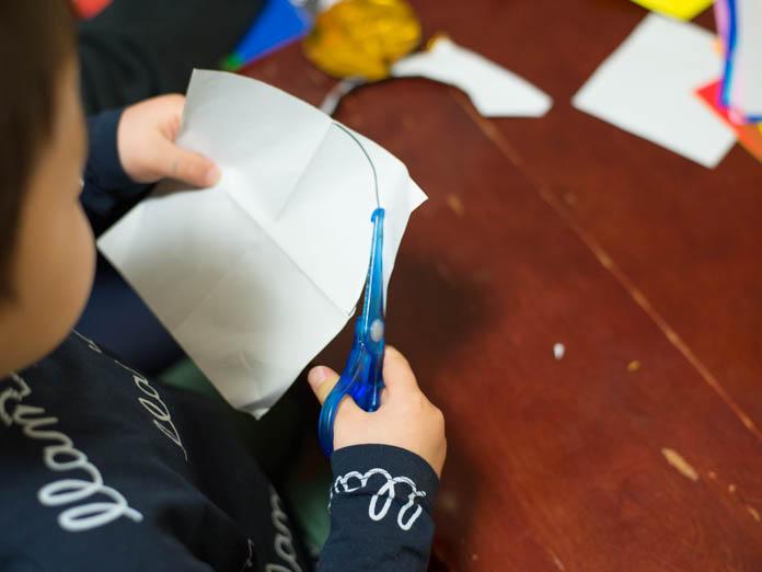 子どもがハサミで折り紙を切っている