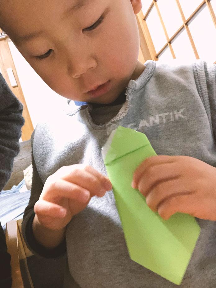 折り紙で作ったネクタイをつける、4歳の息子