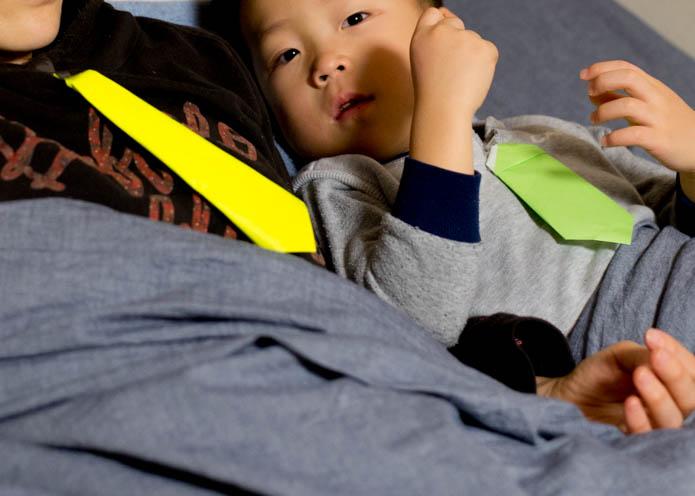 折り紙で作ったネクタイをしめて、ママと寝る息子