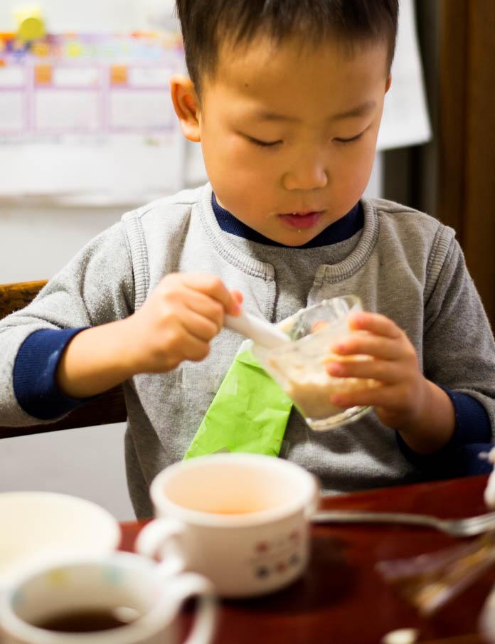 折り紙でつくったネクタイをしめて、朝食を食べる4歳の息子