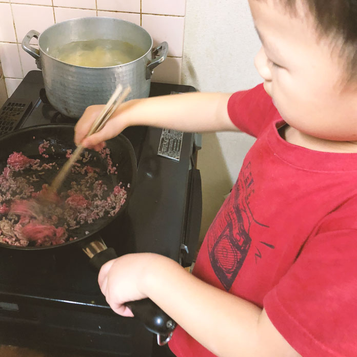 フライパンで炒め物をする男の子