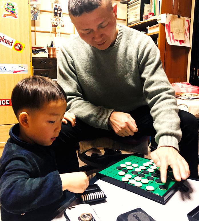 4歳の息子にオセロを教える父親